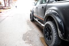 Vista inferior à roda de carro offroad grande no contexto da estrada secundária fotografia de stock