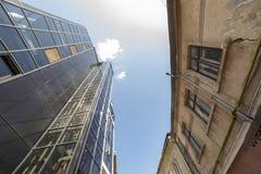 Vista inferior da construção alta com a parede de vidro oposto ao negligenciado crepitado emplastrado no fundo do espaço da cópia foto de stock royalty free