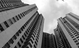 Vista inferior da construção do arranha-céus contra o céu e nuvens cinzentos Olhando acima a vista no prédio de apartamentos na c imagem de stock