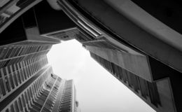 Vista inferior da construção do arranha-céus contra o céu e nuvens cinzentos Olhando acima a vista no prédio de apartamentos na c imagem de stock royalty free