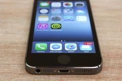 Vista inferior de IPhone 5s que encontra-se na mesa de madeira Fotografia de Stock Royalty Free
