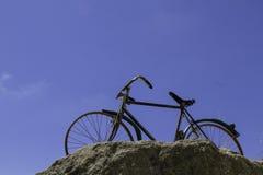 Vista inferior de la bici en roca en fondo del cielo Imagen de archivo libre de regalías