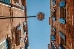 Vista inferior de la lámpara de calle tradicional en una casa veneciana vieja con los pernos de madera en el alambre en la mitad  Fotografía de archivo libre de regalías