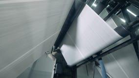 Vista inferior del pedazo de papel sólido que se mueve a través de la máquina de la fábrica almacen de video