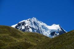 Vista innevata dell'alta montagna dalla valle verde Immagini Stock