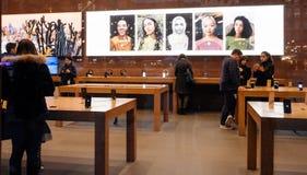 Vista interior de Apple Store com os clientes que compram computadores Imagens de Stock