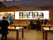Vista interior de Apple Store com os clientes que compram computadores Imagem de Stock Royalty Free