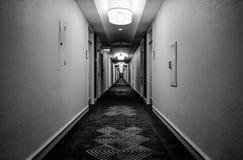 Vista interior de un pasillo del hotel que muestra las diversas puertas del sitio fotografía de archivo