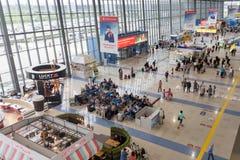 Vista interior do aeroporto internacional de Vladivostok Muitos passageiros que esperam o embarque, o café e as lojas fotografia de stock