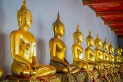 Vista interna de estátuas agradáveis da Buda do ouro em seguido em Wat Pho Temple em Tailândia Foto de Stock