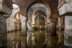 Vista interna della cisterna araba Caceres Spagna, riflessioni degli arché nell'acqua Fotografia Stock Libera da Diritti