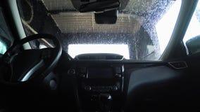 Vista interna di un'automobile che ? lavata su una macchina automatica Autolavaggio dall'interno dell'automobile video d archivio