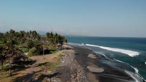 vista 4K aérea da praia preta da areia no leste da ilha tropical de Bali, Indonésia video estoque