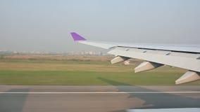 a vista 4K da janela do avião tocou para baixo na pista de decolagem em Banguecoque vídeos de arquivo