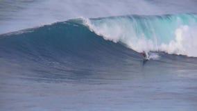 Vista 4k maravilhosa no surfista profissional que executa os conluios que montam ondas espumosas enormes do azul de turquesa no s vídeos de arquivo
