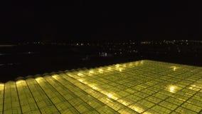 Vista a la baja aérea del invernadero con la iluminación artificial almacen de metraje de vídeo