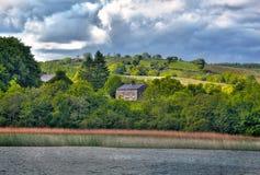 Vista a la casa irlandesa en el río Shannon Foto de archivo libre de regalías