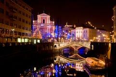 Vista a la iglesia de St Francis y a tres puentes, con el río de Ljubljanica corriendo abajo, adornado por días de fiesta de los  Foto de archivo
