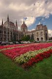 Vista larga da construção do parlamento em Budapest, em Hungria e em jardim com flores Fotos de Stock