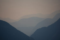 Vista larga em um vale durante o por do sol nos cumes Fotos de Stock Royalty Free