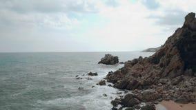 Vista lateral aérea de las olas oceánicas que golpean la playa arenosa debajo del acantilado en el mar Mediterráneo metrajes