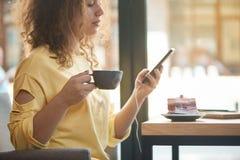 Vista lateral cosechada del café de consumición de la muchacha, escuchando la música en restaurante foto de archivo