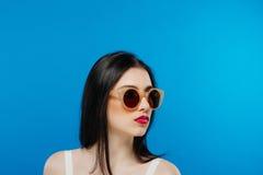 Vista lateral da cara fêmea com os óculos de sol perfeitos limpos da pele e da forma no fundo azul imagens de stock