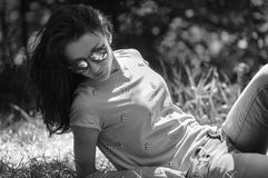 Vista lateral da morena atrativa nos óculos de sol elegantes que encontram-se na terra durante Sunny Day no verão Preto e Foto de Stock