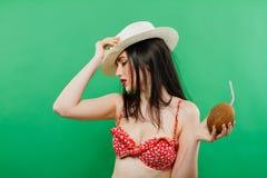 Vista lateral da morena com vaqueiro Hat e cabelo longo no roupa de banho vermelho que guarda o cocktail do coco em suas mãos no  fotografia de stock royalty free