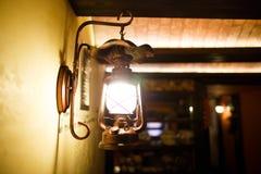 A vista lateral das lâmpadas de brilho do vintage que haning na parede no café de madeira Imagem de Stock Royalty Free