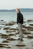 Vista lateral de adolescente masculino en vaqueros en la playa Imagenes de archivo