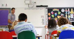 Vista lateral de alunos de ensino caucasianos do professor masculino no whiteboard na sala de aula 4k vídeos de arquivo