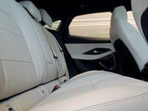 Vista lateral de asientos posteriores en interior del coche con tapicería de cuero blanco y negro foto de archivo