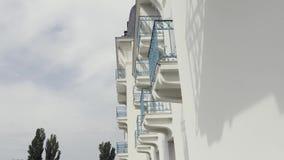 Vista lateral de balcones con la verja azul del hierro labrado del edificio moderno, fondo arquitectónico acci?n Pared blanca almacen de video