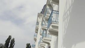 Vista lateral de balcones con la verja azul del hierro labrado del edificio moderno, fondo arquitectónico acci?n Pared blanca metrajes