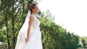 Vista lateral de debajo de una novia feliz joven en un vestido blanco almacen de video