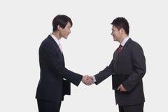 Vista lateral de dos hombres de negocios sonrientes que sacuden las manos, tiro del estudio Imagen de archivo libre de regalías