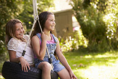 Vista lateral de dos muchachas que juegan en el oscilación del neumático en jardín Imágenes de archivo libres de regalías