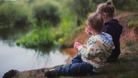 Vista lateral de dos niños lindos, muchacho y muchacha, comiendo la sandía, sentándose en una orilla del río almacen de metraje de vídeo