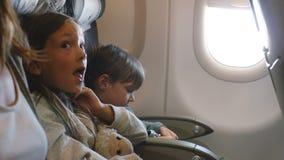 Vista lateral de dos pequeños niños aburridos que miran alrededor durante el vuelo largo del aeroplano que viene acompañado a las metrajes
