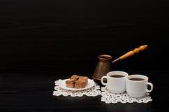 Vista lateral de dos tazas de café en las servilletas del cordón, el postre del chocolate y los potes turcos Fotos de archivo libres de regalías
