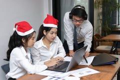 Vista lateral de hombres de negocios asiáticos jovenes alegres en los sombreros de Papá Noel usando el ordenador portátil en ofic foto de archivo