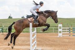 Vista lateral de la amazona de pelo largo que salta en un caballo Fotografía de archivo libre de regalías