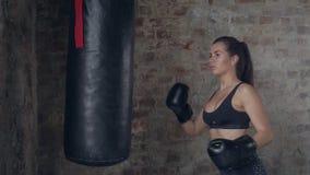 Vista lateral de la chica joven en técnica negra del entrenamiento de los guantes de boxeo con el saco de arena almacen de video