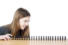 Vista lateral de la chica joven lista para empujar el primer dominó en fila aislado en el fondo blanco Imagen de archivo libre de regalías