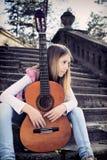 Vista lateral de la chica joven soñadora con la guitarra que se sienta en las escaleras Foto de archivo libre de regalías