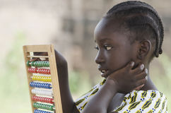 Vista lateral de la colegiala africana que aprende en el ábaco imágenes de archivo libres de regalías