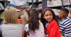 Vista lateral de la colegiala asiática que mira detrás y que sonríe en la biblioteca escolar 4k metrajes