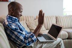 Vista lateral de la comunicación video del hombre mayor en casa imagen de archivo