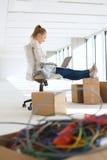 Vista lateral de la empresaria joven que usa el ordenador portátil con los pies para arriba en la caja de cartón en oficina Foto de archivo